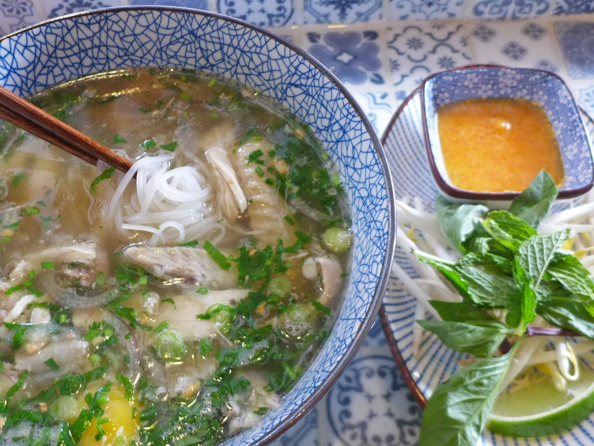 A chicken pho with an orange ginger dipping sauce for the morsels of poultry, and a raw egg floats just under the surface.