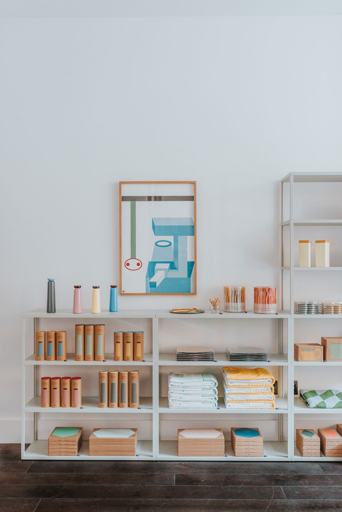 White metal shelves with colorful water bottles, containers, and towels. There is a geometric print hanging on the wall in a wooden frame.
