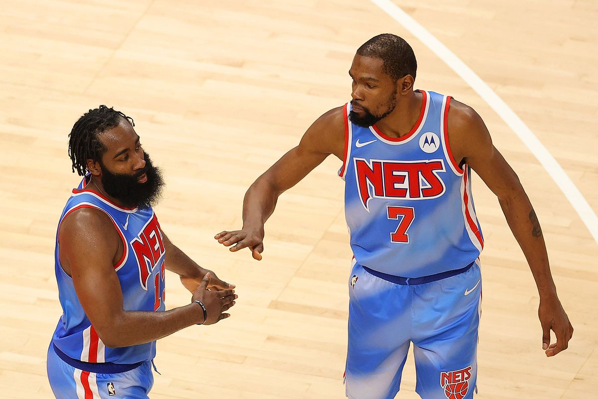 James Harden #13 and Kevin Durant #7 of the Brooklyn Nets react during overtime against the Atlanta Hawks at State Farm Arena on January 27, 2021 in Atlanta, Georgia.