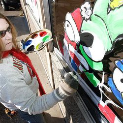 Tammy Farley paints windows at Christmas time with holiday images. Farley paints a fun sledding scene at an Orem business on Dec. 12, 2005.