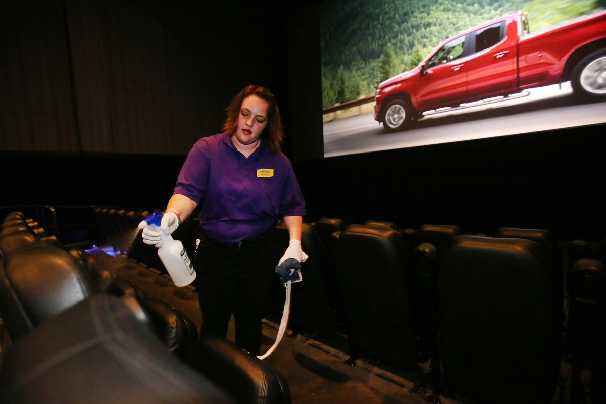 McKenzie Horrocks cleans the seats and food trays between movies at the Megaplex Theatres at Jordan Commons in Sandy on Friday, March 13, 2020.