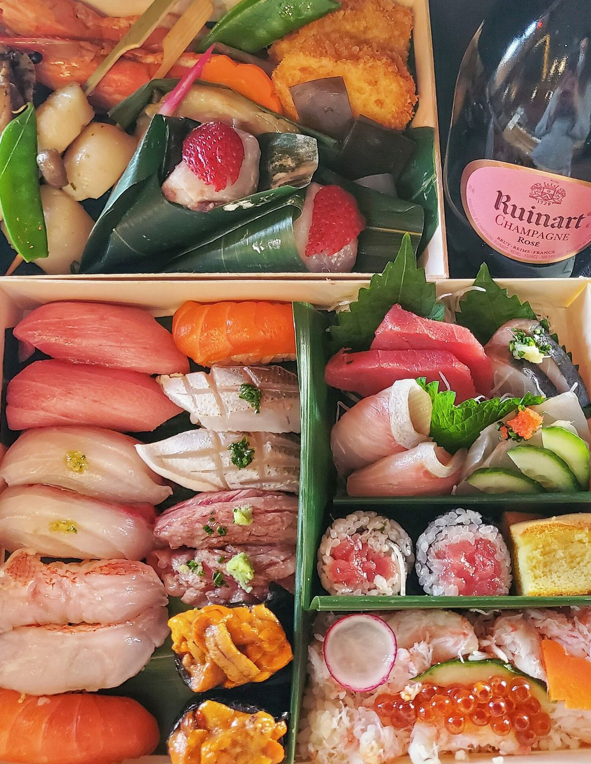 Valentine's Day takeout option from Omakase, a box full of colorful sushi and veggies. There's a bottle of champagne in the top right corner.