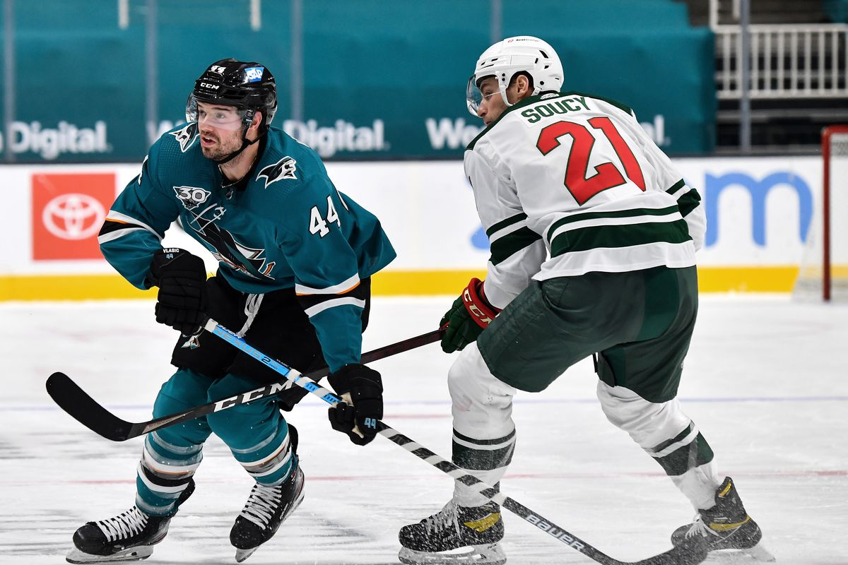 Marc-Edouard Vlasic #44 of the San Jose Sharks battles for position against Carson Soucy #21 of the Minnesota Wild at SAP Center on February 22, 2021 in San Jose, California.