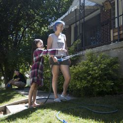 Jill Eagleton, right, waters her lawn with her daughter, Tayte, 8, while her husband, Seth, plays with their 8-week-old fox at their home in Salt Lake City on June 19, 2017. Jill explained that she was watering the dead grass where the sprinkler doesn't reach.