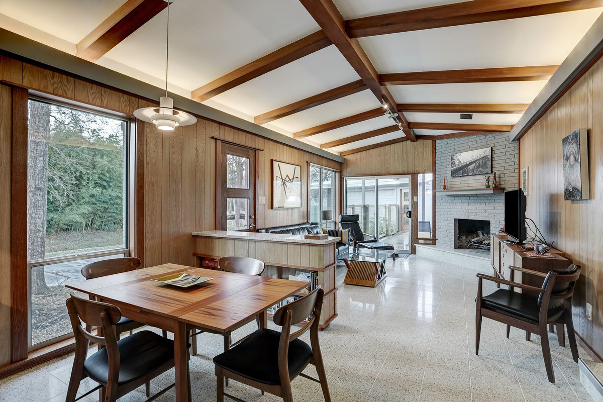 A living room has peaked ceilings with exposed beams, light terrazzo tile, and a fireplace in the corner.