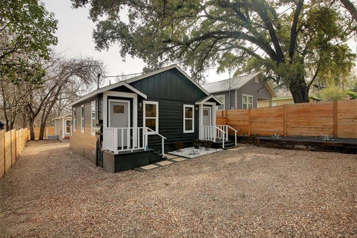 Dark gray wooden house/duplex with white trim, doors on each side, gravel parking/yard