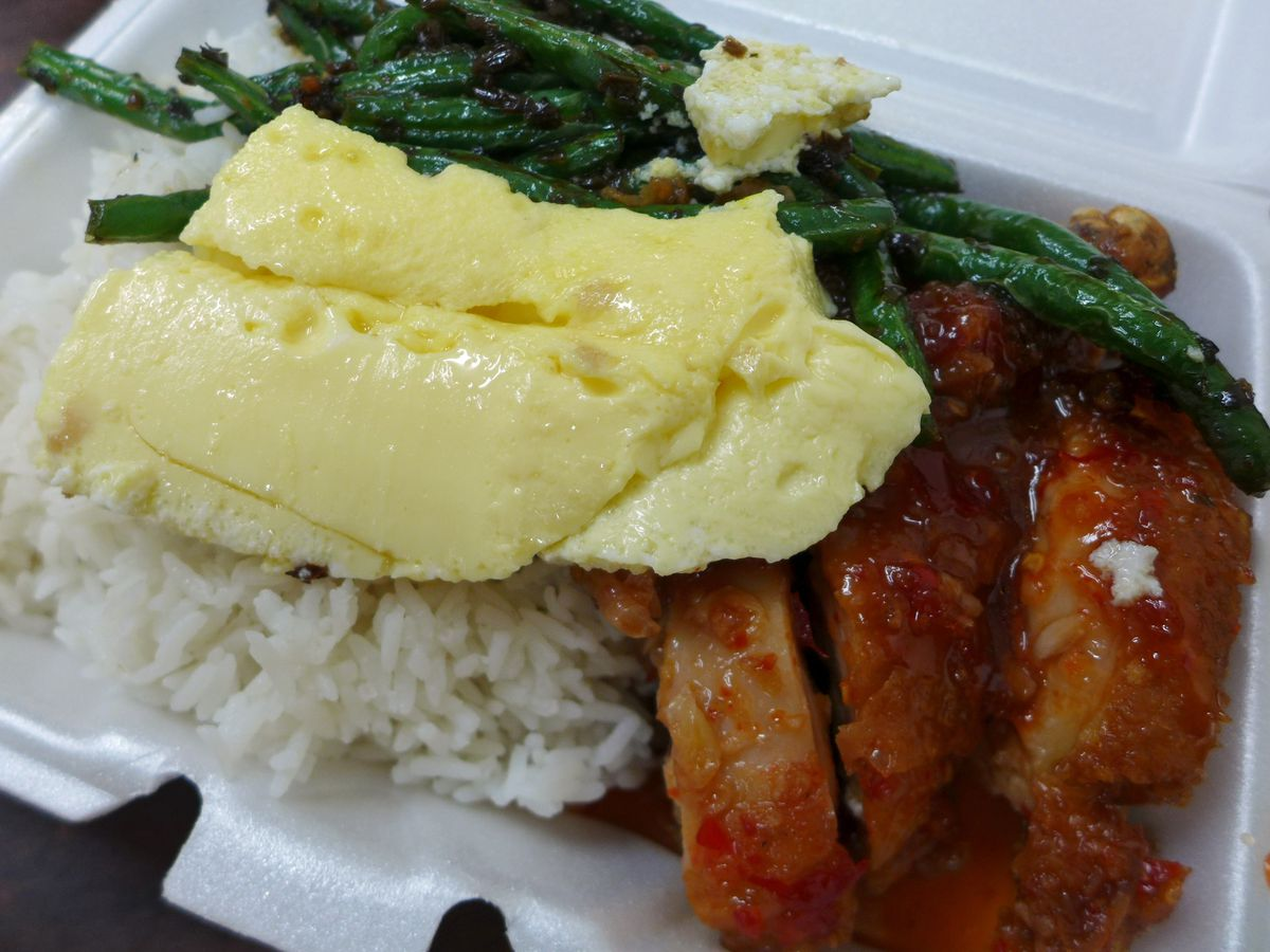 Over rice with three dishes, chicken, green beans, omelet.