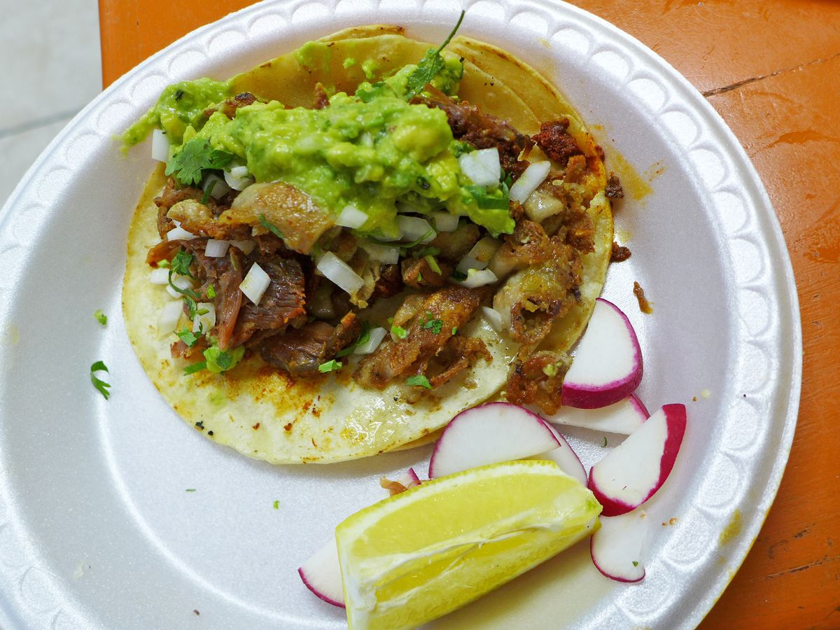 A flat glistening tortilla with meat and guacamole, with a lemon wedge on the side.