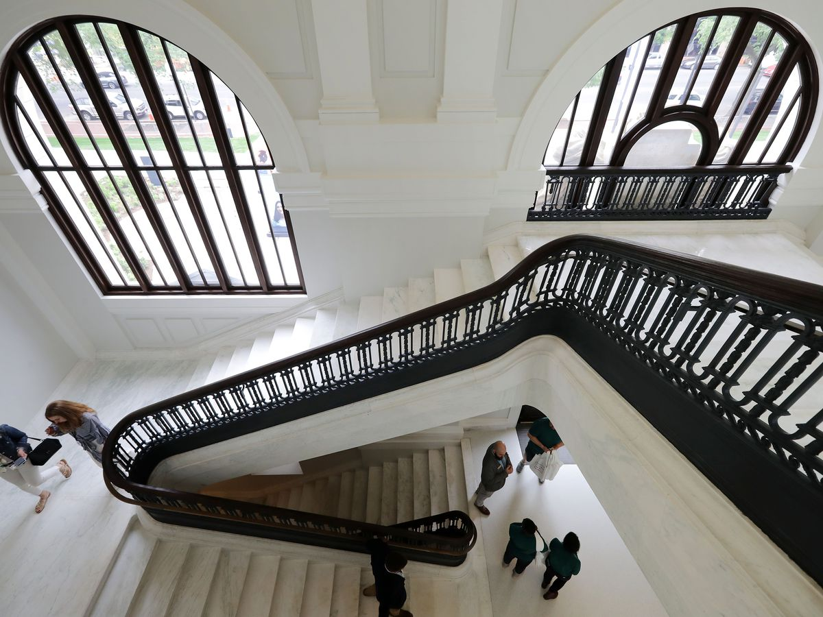 A curved stairwell inside a neoclassical library. It has big arched windows.