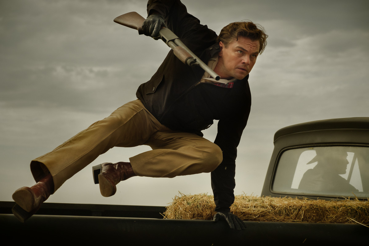 Leonardo DiCaprio vaults off a pickup truck, rifle in hand, in Once Upon a Time in Hollywood.