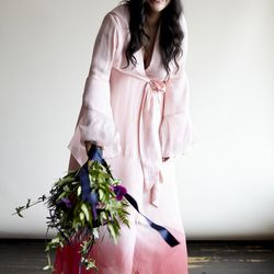 A high drama, ombré rose silk crepe dress. It also features silk chiffon bell sleeves and a sunset sash.