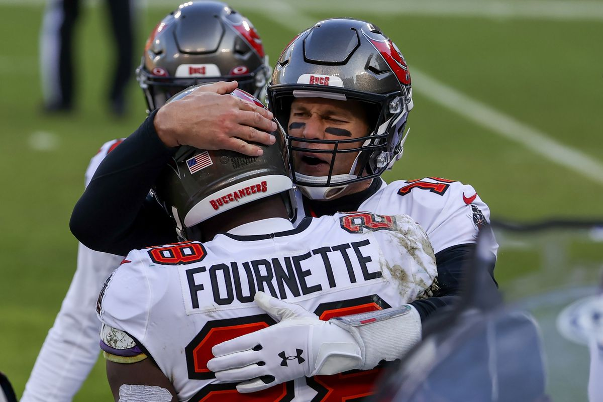 Leonard Fournette #28 and Tom Brady #12 of the Tampa Bay Buccaneers celebrate after Fournette scored a touchdown in the second quarter against the Green Bay Packers during the NFC Championship game at Lambeau Field on January 24, 2021 in Green Bay, Wisconsin.