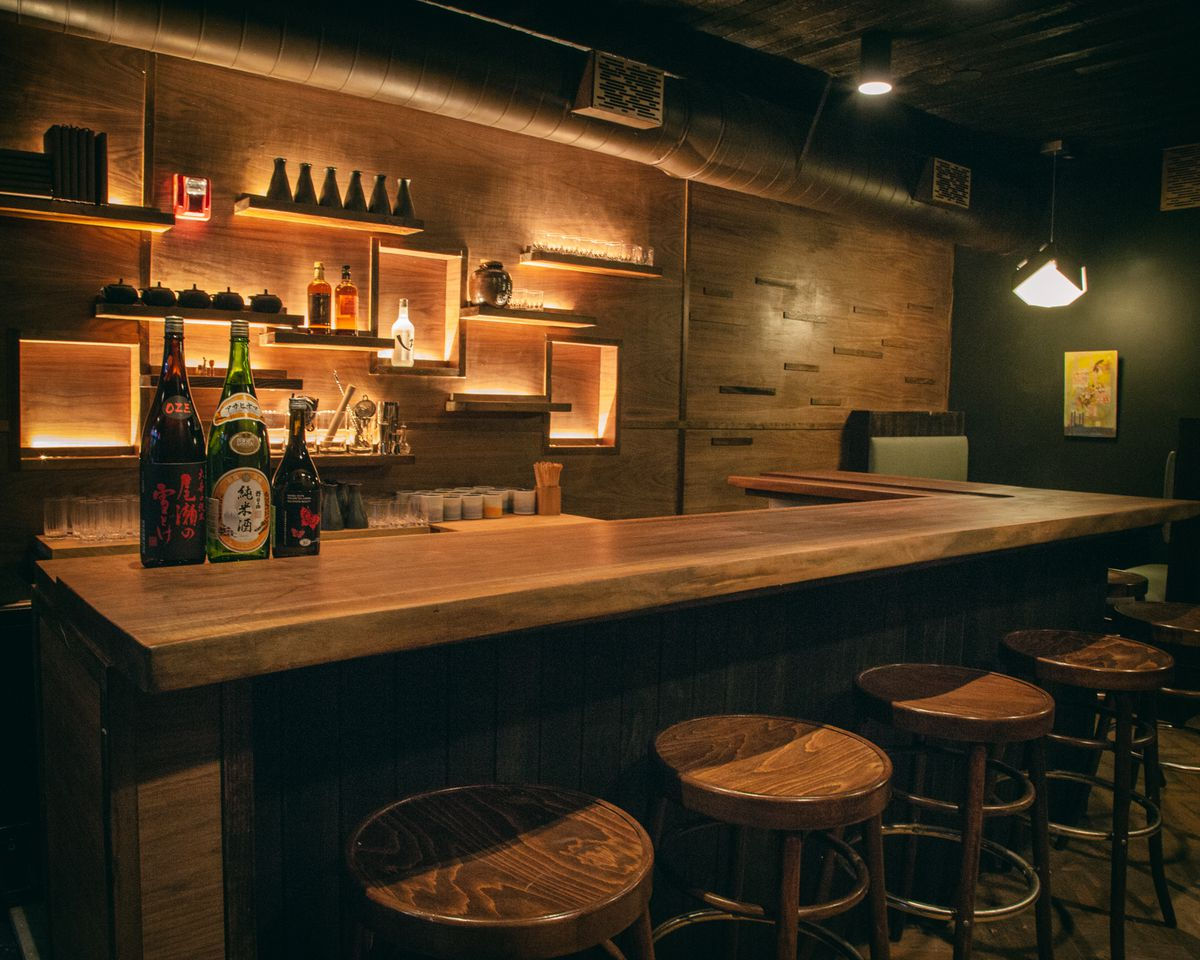 a bar with bar stools and shelves with sake