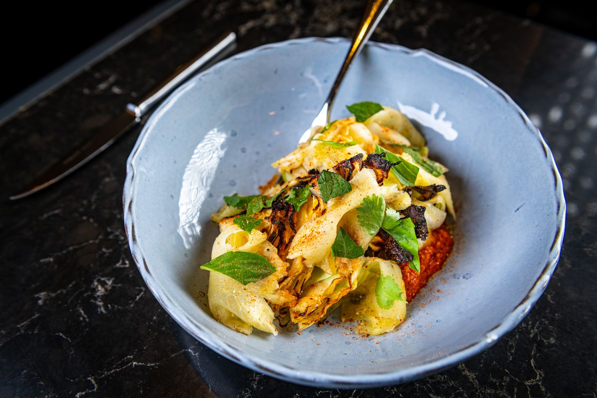 Charred Carafalex cabbage at Moon Rabbit comes with slices of pineapple and a spicy peanut romesco sauce meant to evoke bún bò huế