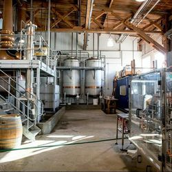 Inside the distillery, with the hand-hammered copper still (left), the holding tanks for the corn-based, neutral spirit (center), and the bottling machine (right).