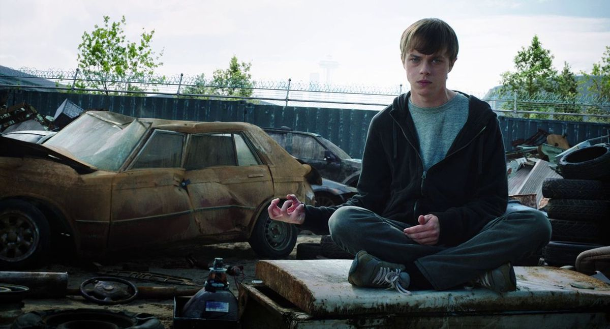 in Chronicle, a young brown-haired man sits cross-legged at a junkyard scrunching the air with his right hand to crush a car behind him