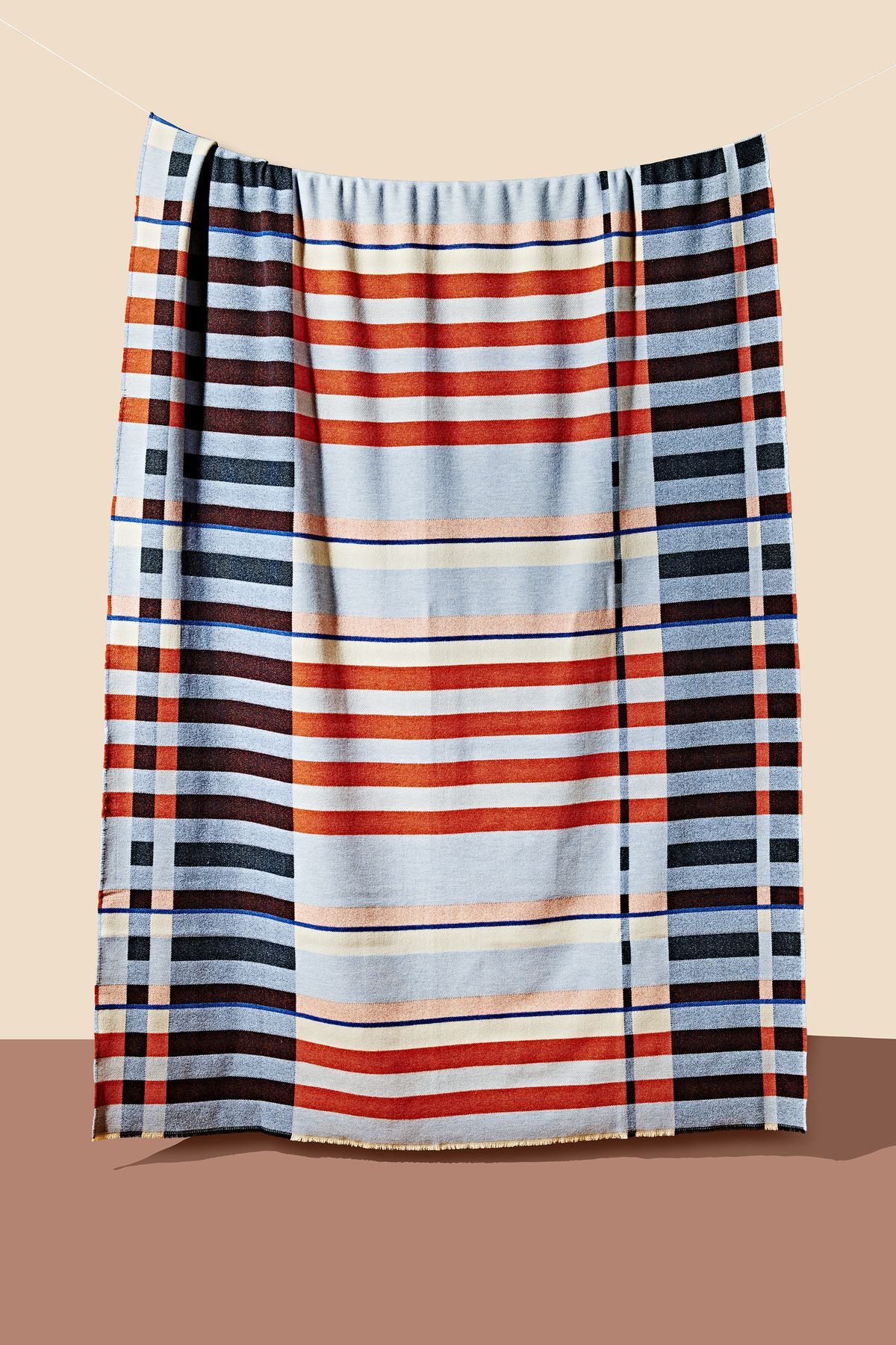 A blanket with intersecting colorful stripes which is similar to a dorm blanket design by Bauhaus weaver Gunta Stolzl. The blanket is part of the Curbed Holiday Gift Guide 2019.