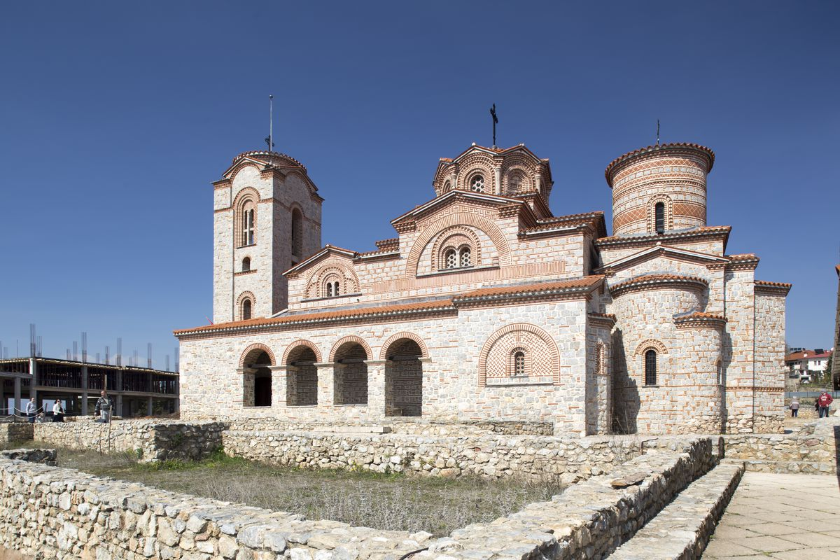 """The exterior of <span data-author=""""843"""">Saint Panteleimon church in Macedonia. The facade is stone and mortar and there are multiple domes on the roof.</span>"""