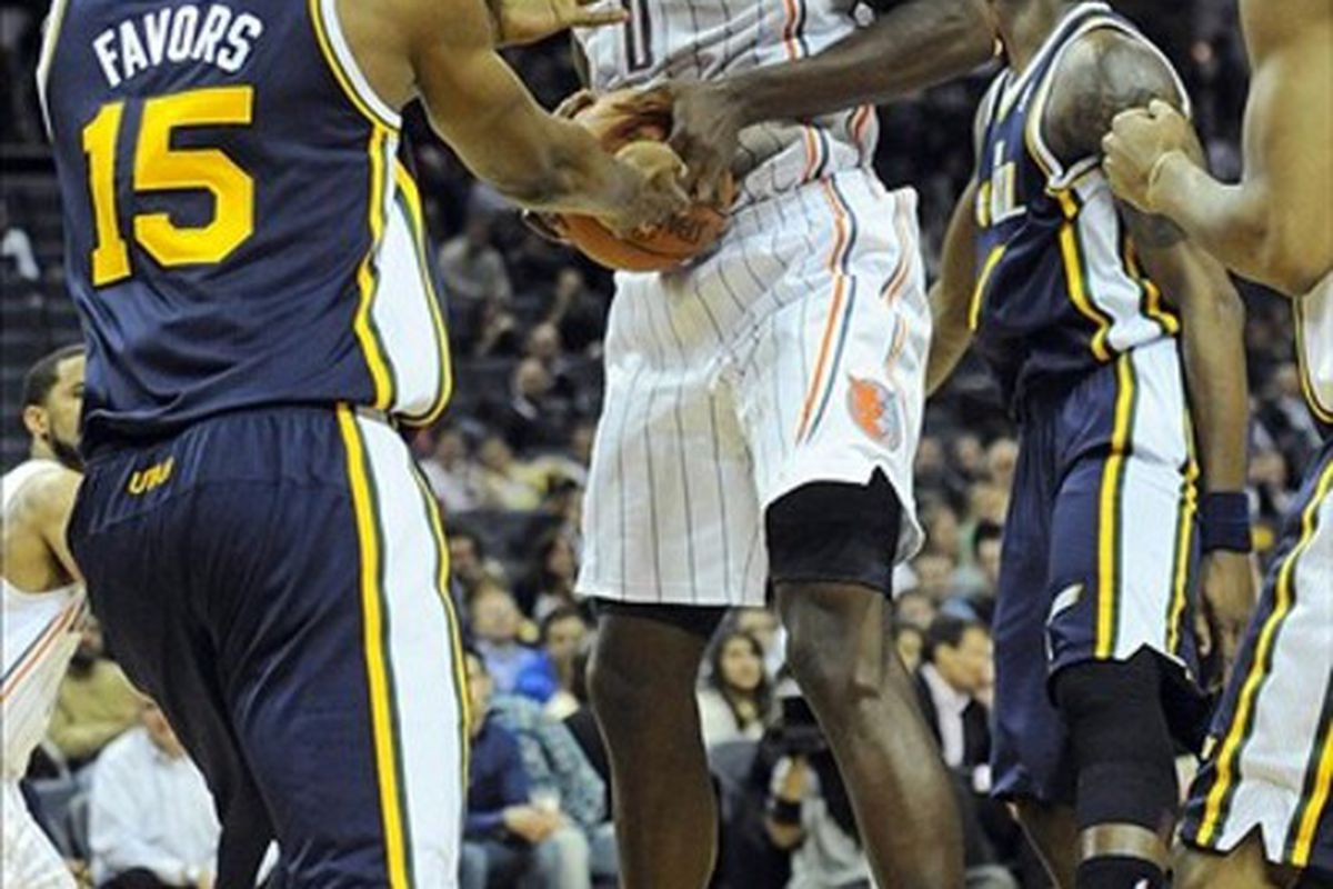 March 7, 2012; Charlotte, NC, USA; Charlotte Bobcats center Bismack Biyombo (0) gets a rebound from Utah Bobcats forward center Derrick Favors (15) during the game at Time Warner Cable Arena. Jazz win 99-93. Mandatory Credit: Sam Sharpe-US PRESSWIRE