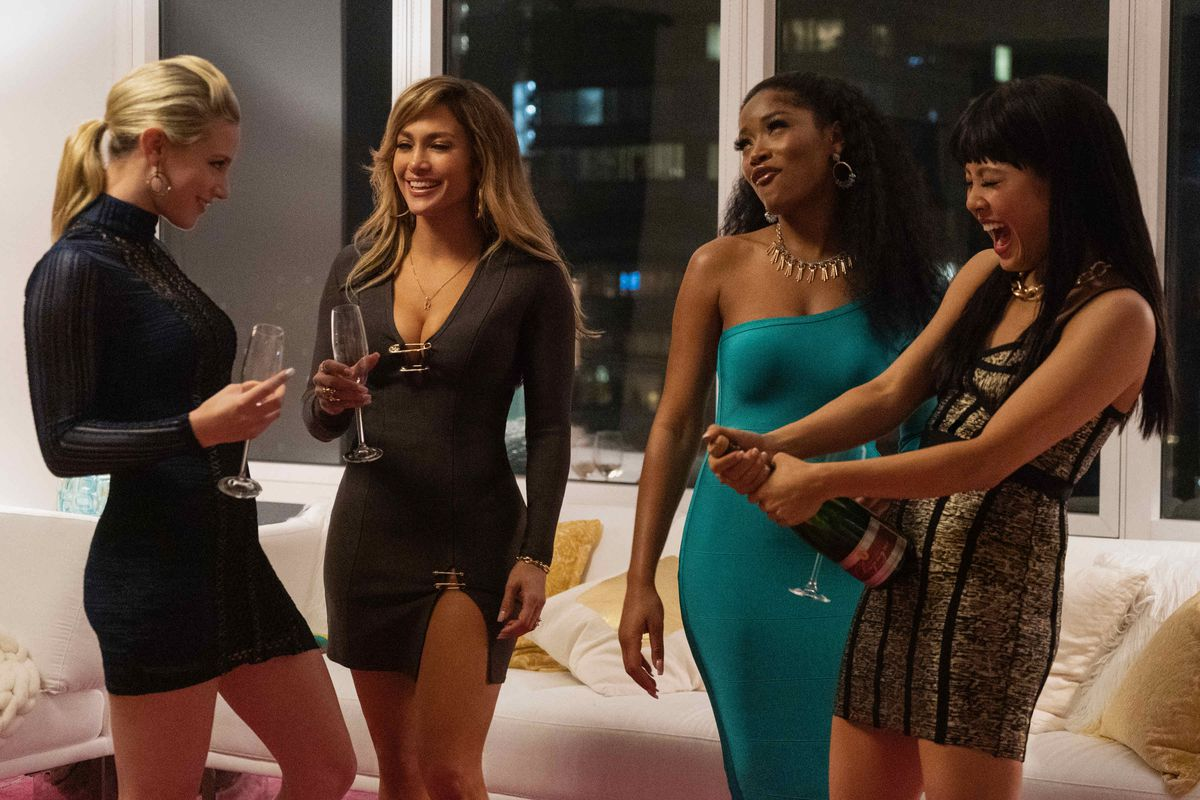 """The actresses in a scene from the movie """"Hustlers"""" —Lili Reinhart, Jennifer Lopez, Keke Palmer, and Constance Wu — stand together in a high-rise apartment and pop a bottle of champagne."""