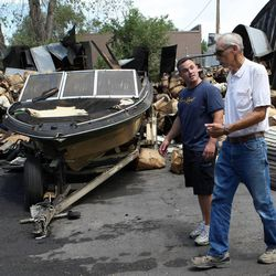 Shane Wimmer and his grandfather Arden Wimmer check out the damage after an early morning fire destroyed 22 storage units in Millcreek on Friday, July 27, 2012. The Wimmers' storage units were not damaged.