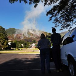 Julie and Craig Baker of Kaysville take some time out of their date night to watch Crews work a fire burning on the mountain above Farmington on Friday, June 23, 2017.