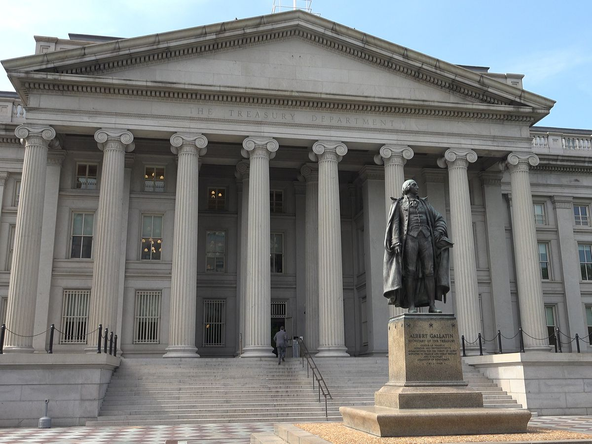 The exterior of the United States treasury in Washington D.C. The facade has columns and a statue of a man in front.