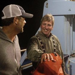 In this Sept. 13, 2012, photo, Massachusetts shark expert Greg Skomal, right, and expedition leader Chris Fischer discuss their success after tagging their first Atlantic great white shark on the research vessel Ocearch off the coast of Chatham, Mass. Skomal named the nearly 15-foot, 2,292-pound female shark Genie for famed shark researcher Eugenie Clark. The Ocearch team baits the fish and leads them onto a lift, tagging and taking blood, tissue and semen samples up close from the world's most feared predator. The real-time satellite tag tracks the shark each time its dorsal fin breaks the surface, plotting its location on a map.