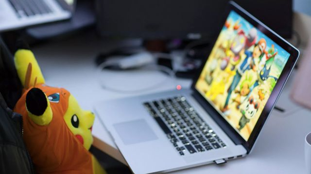 a Pikachu Build-a-Bear looking at a MacBook