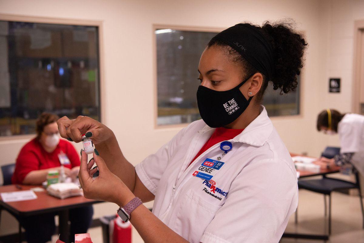 An H-E-B pharmacist preparing a COVID-19 vaccine dose