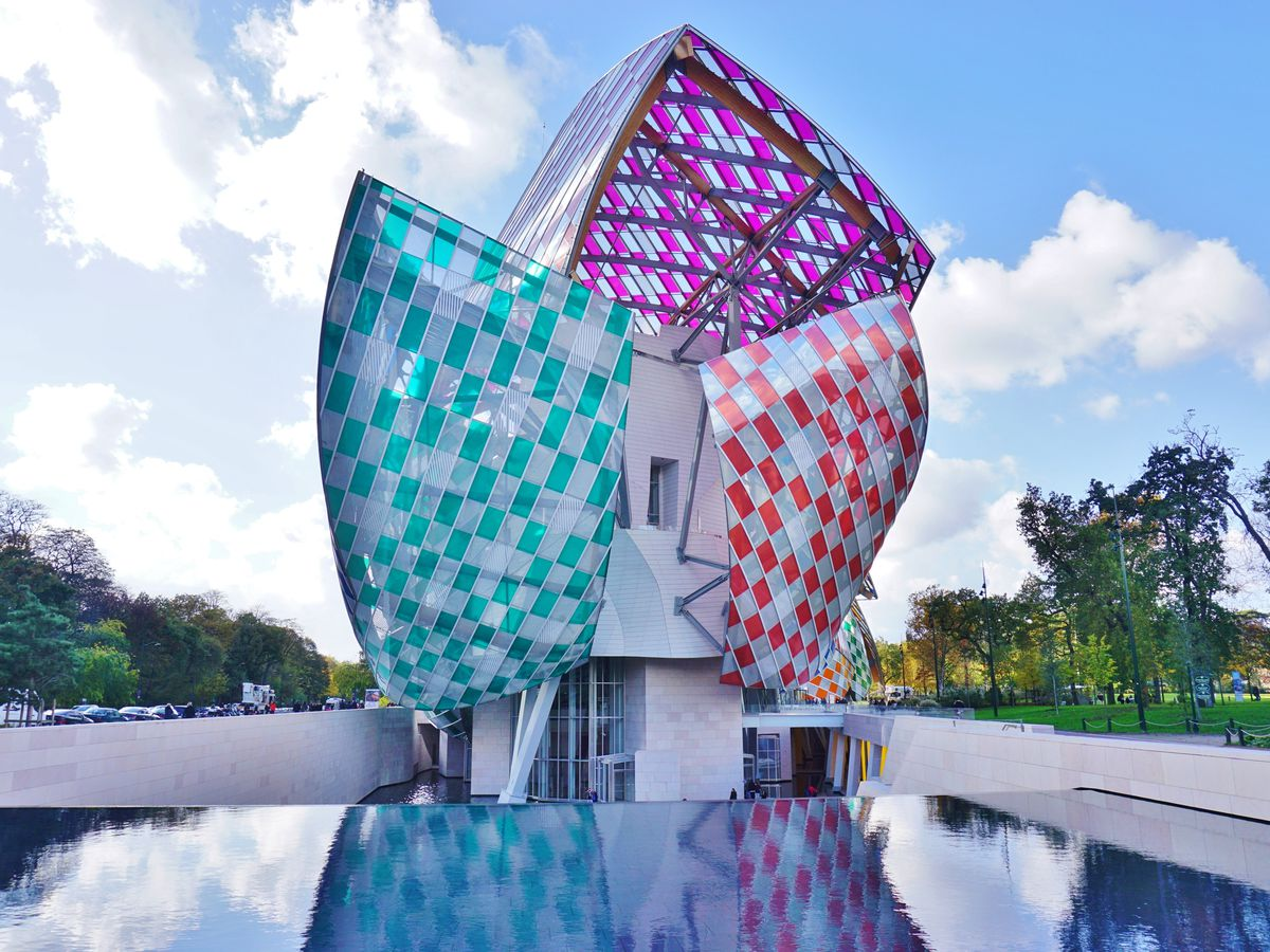 The exterior of the Louis Vuitton Foundation building. The facade is glass and steel and multicolored. The structure resembles a sailing ship. In the foreground is a still water fountain.