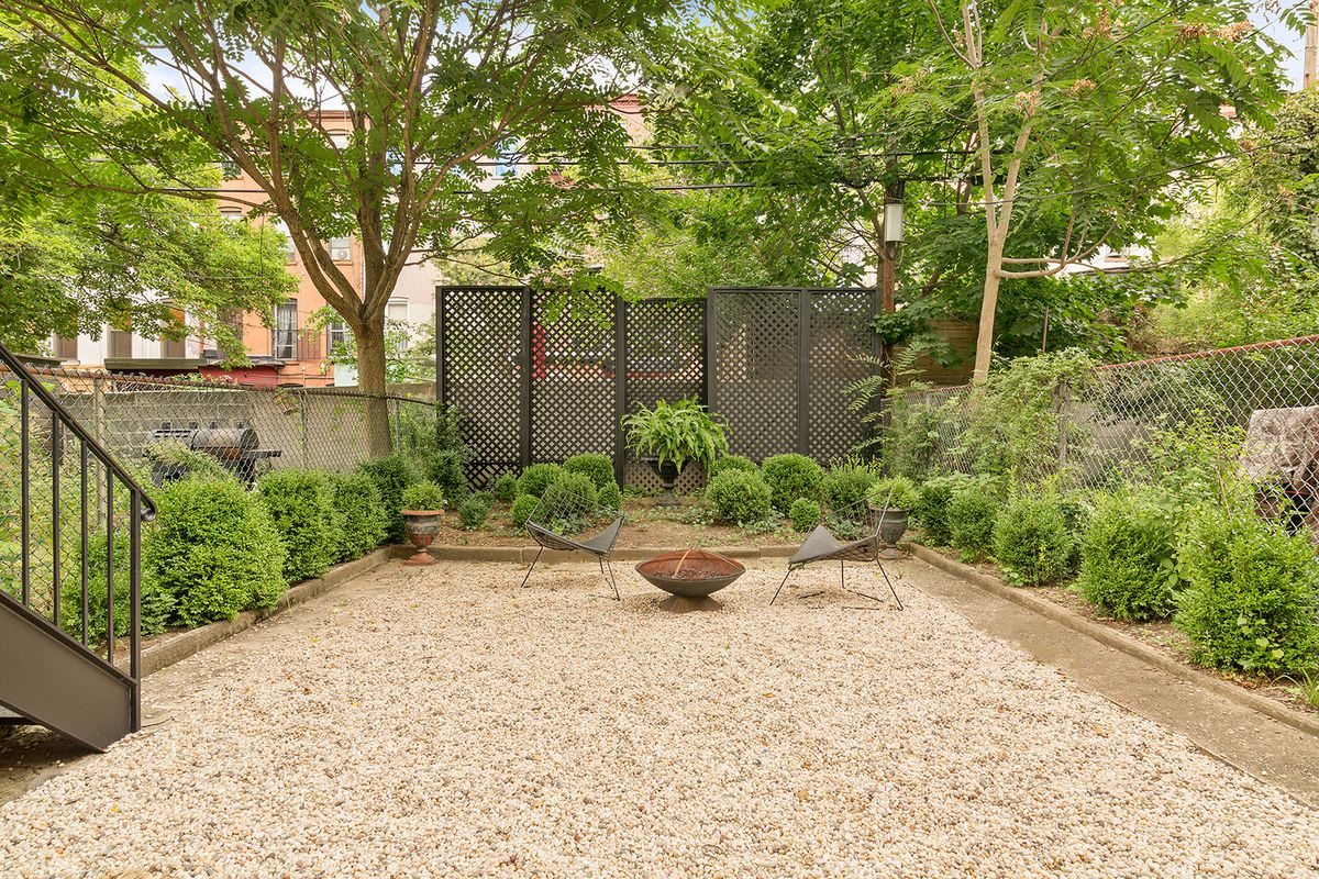 A deep rear garden is lined by beds with bushes.