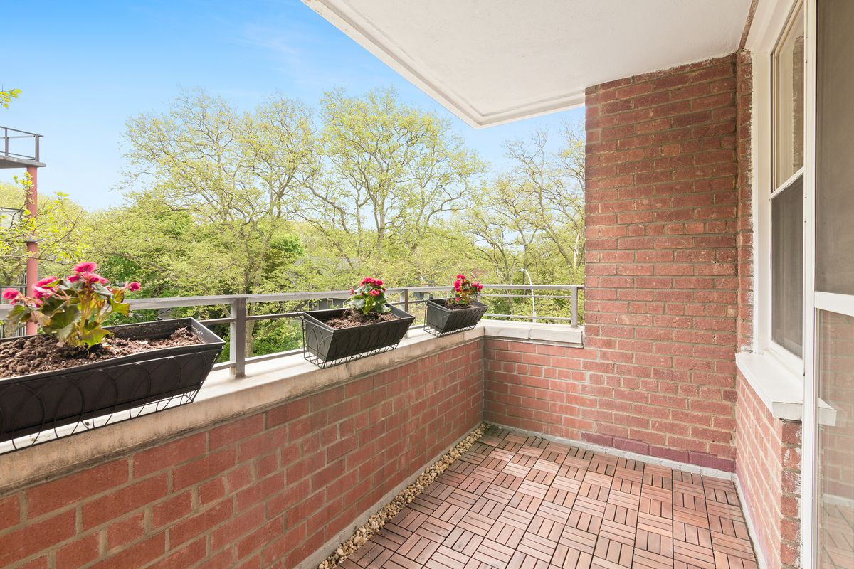 A terrace with brick walls and three planters.
