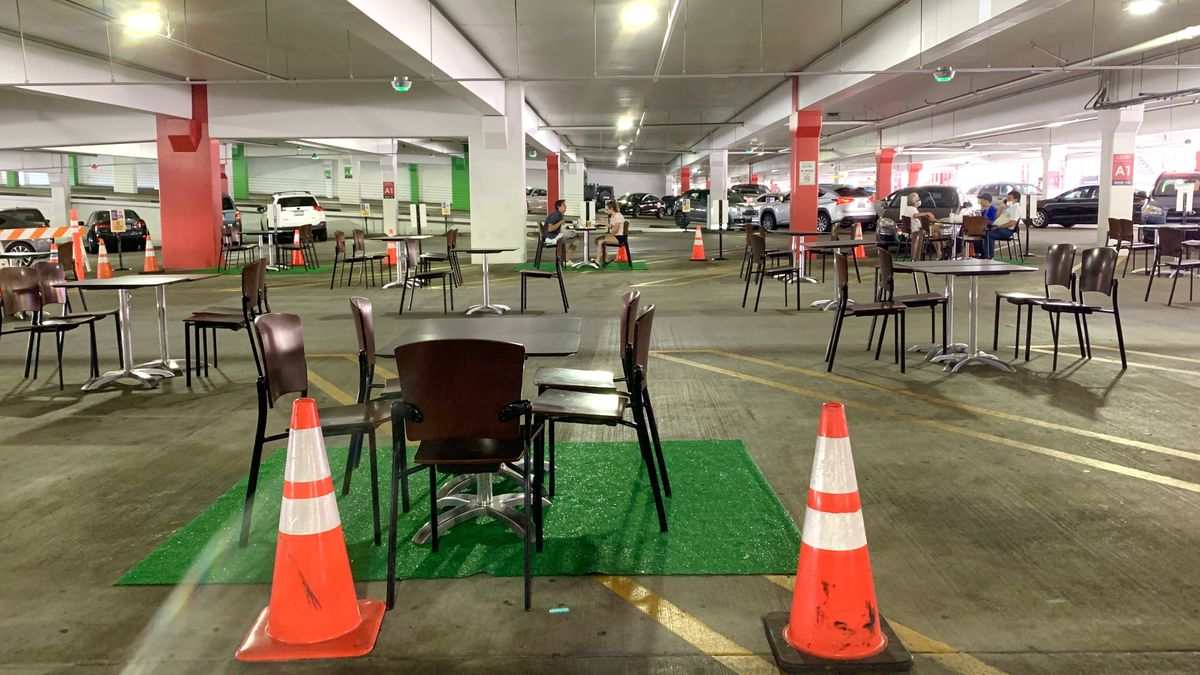 A table set up in a parking garage is surrounded by cones and astroturf as part of an outdoor dining program at Glendale Galleria in Los Angeles.