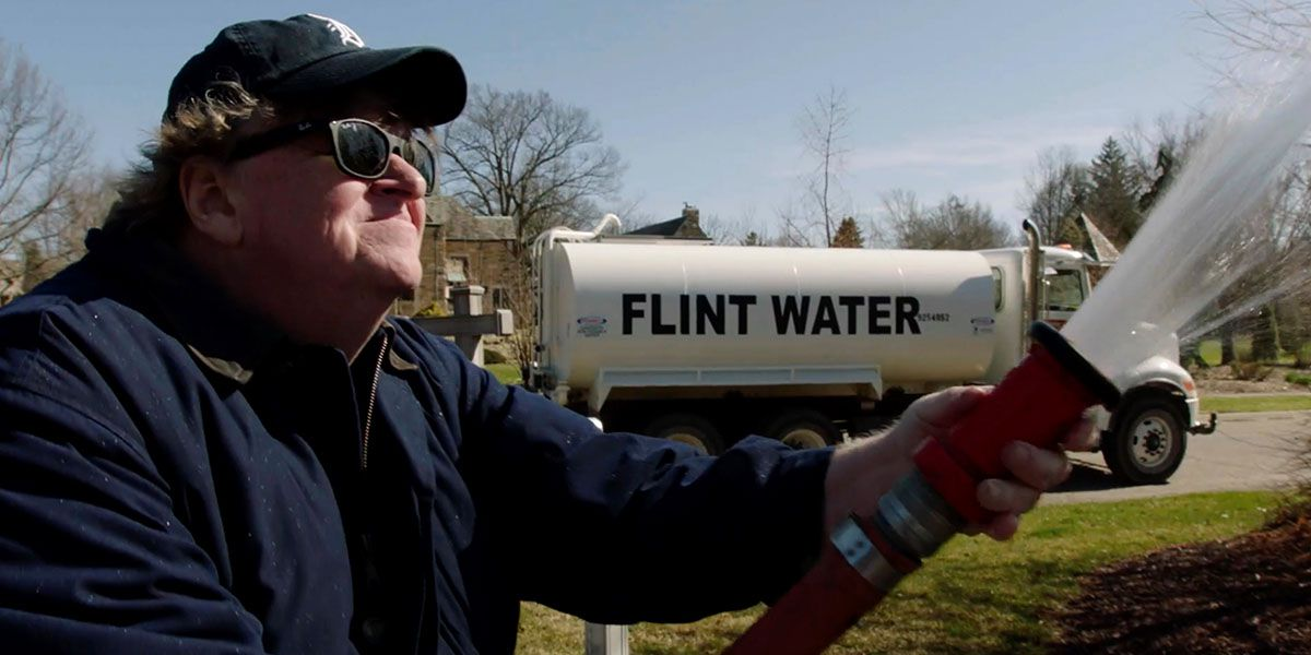 Moore sprays water from Flint, Michigan on Governor Rick Snyder's mansion in his new documentary Fahrenheit 11/9.