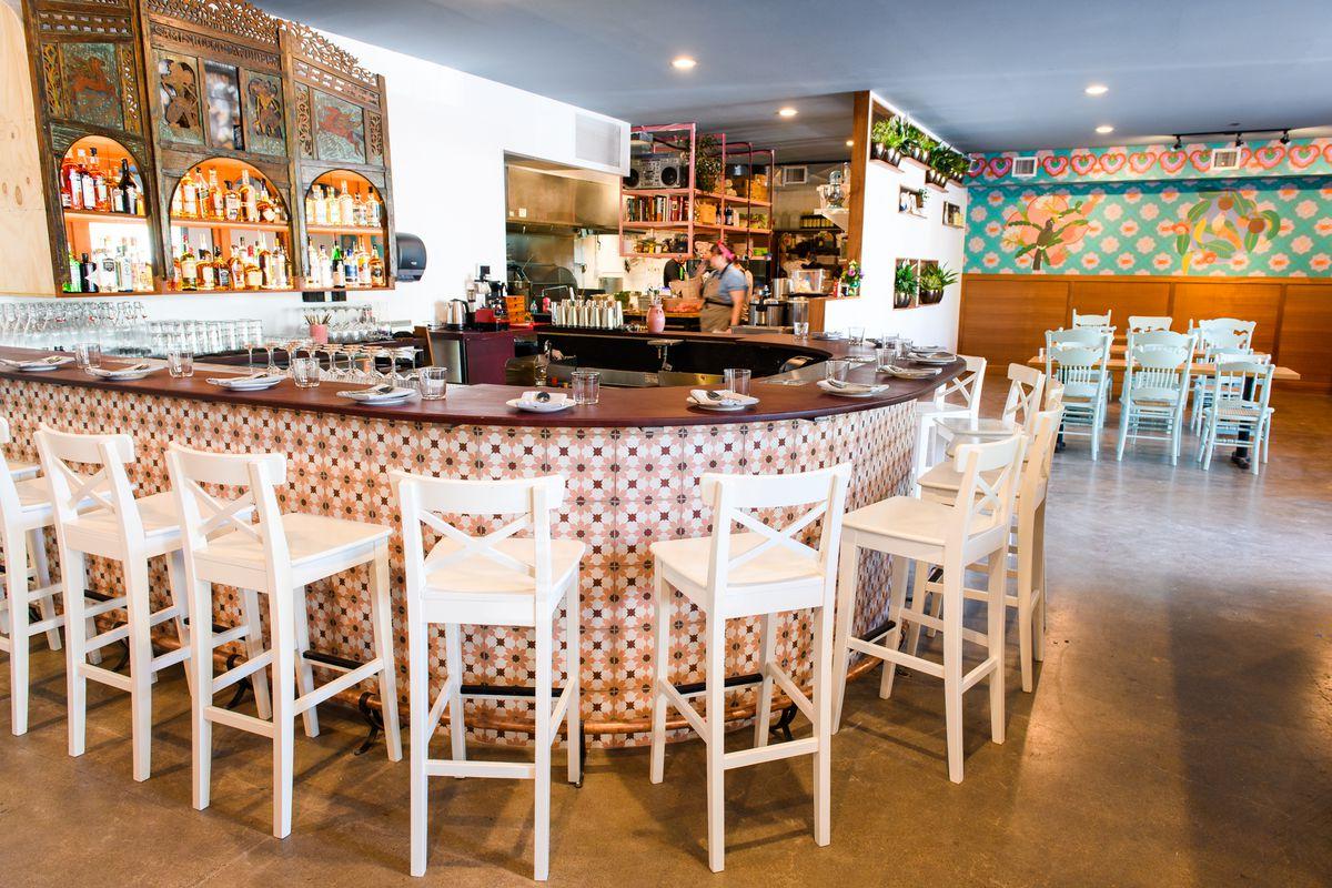 A round bar at Gado Gado, with white chairs