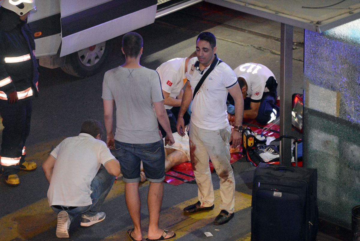 Turkish rescue services help a wounded person outside Ataturk Airport in Istanbul on Tuesday. | Ismail Coskun, IHA via AP