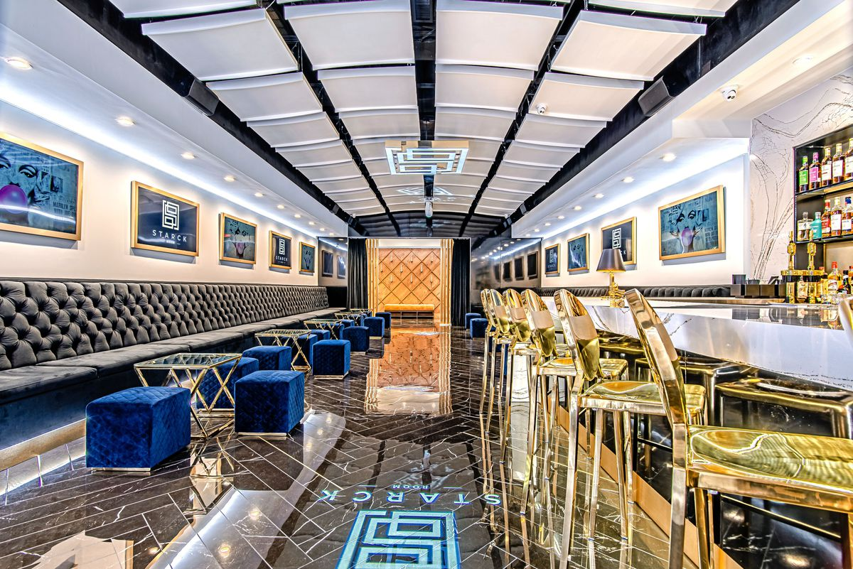 the inside of a bar with blue velvet benches on the left and tall gold bar chairs on the right