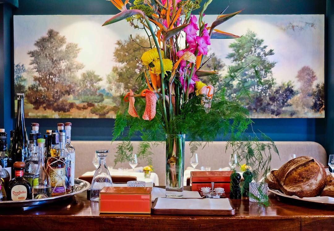 A side table in a dining room with a vase of flowers, bread basket, and spirits