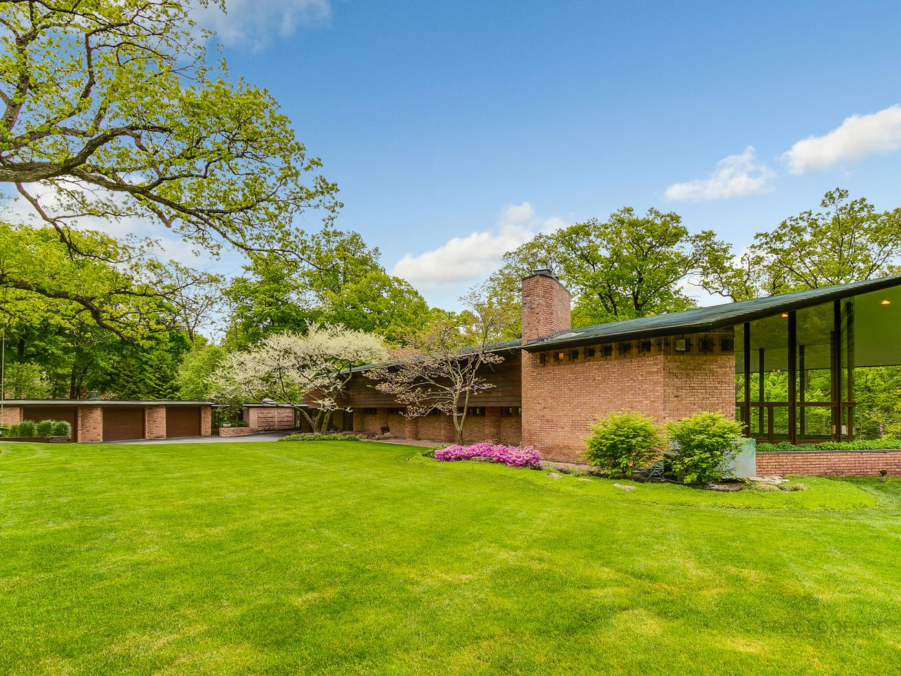 An exterior view of a Frank Lloyd Wright Usonian house designed for Charles F. Glore. There is a large grass lawn and red brick building that slopes into a double height glass living room.