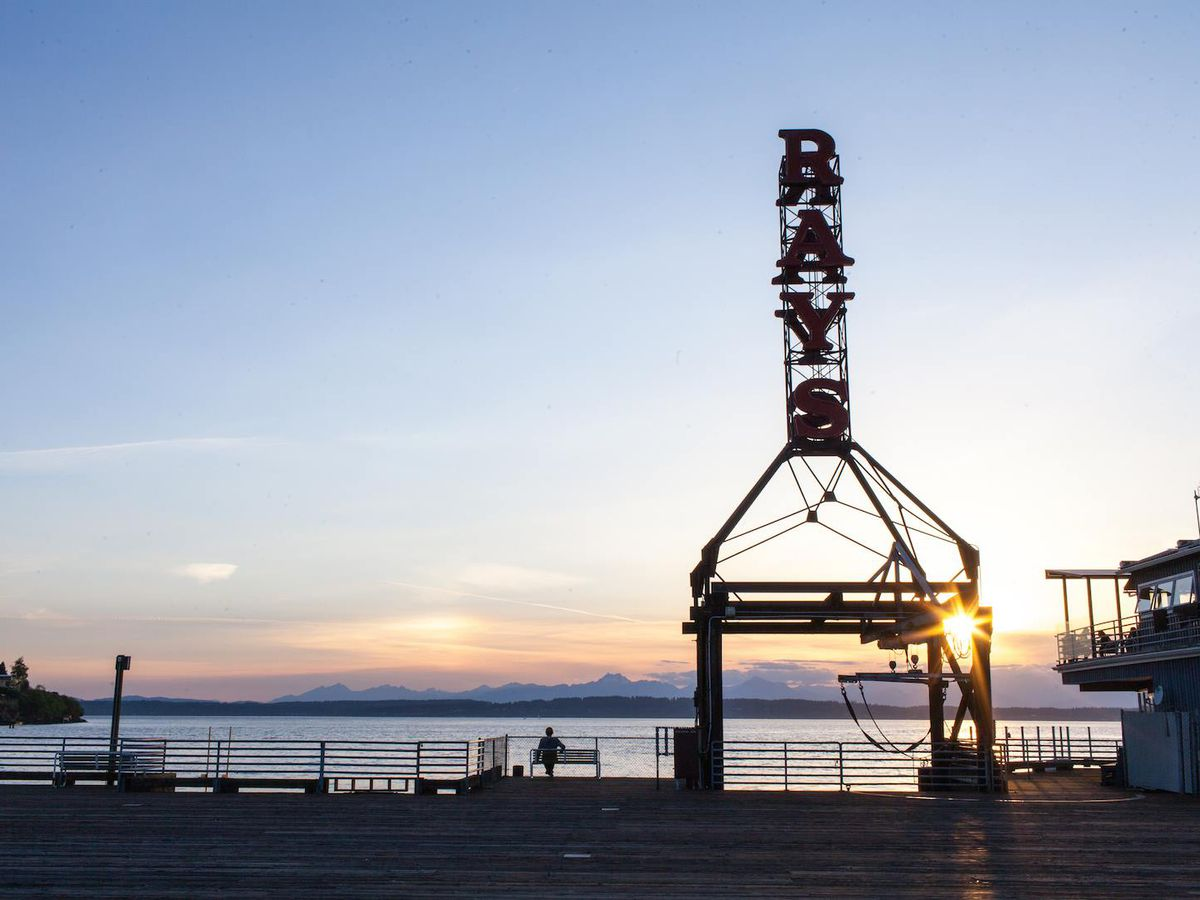 The tall sign at Ray's Boathouse with the Olympic Mountains and Puget Sound at sunset in the background.