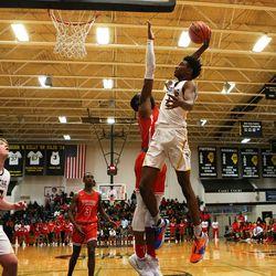 Marian Catholic's Elijah Jones (4) goes hard to the basket and gets the bucket over Homewood-Flossmoor's R.J. Ogom (23).