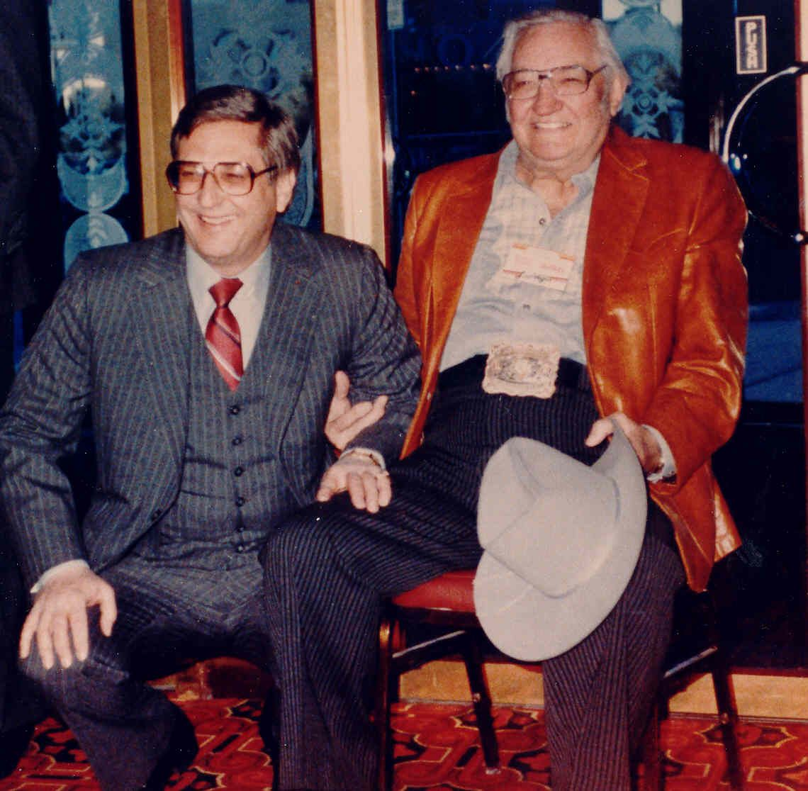 Two men pose for a photo while sitting