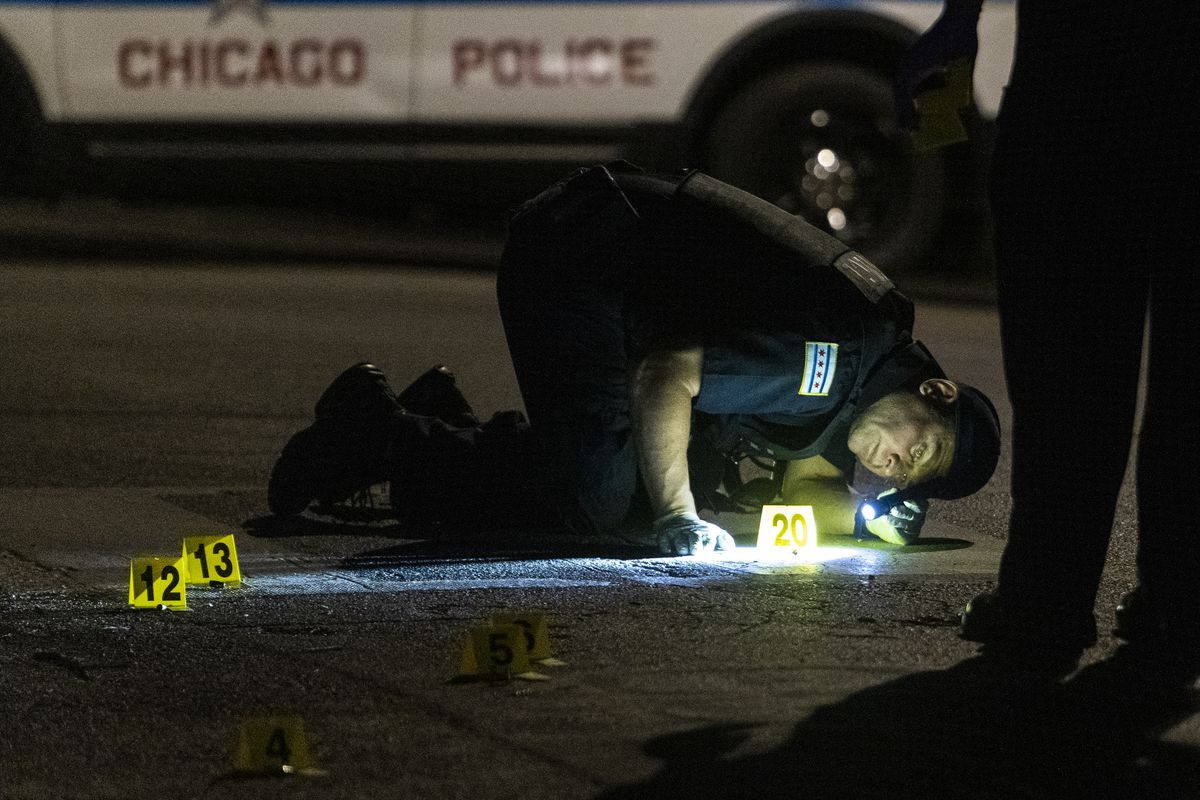 Chicago police investigate the scene where two people were shot August 17, 2020, including a 14-year-old boy and a 17-year-old girl in Bronzeville.