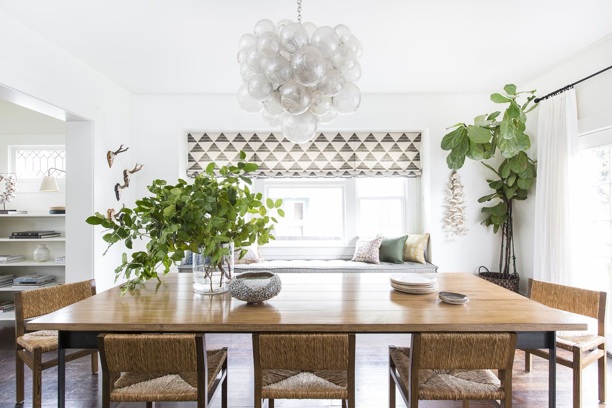 The dining room has a large light fixtures with clear resin bubble-like globes. It hangs over a table with a light-colored wood top.