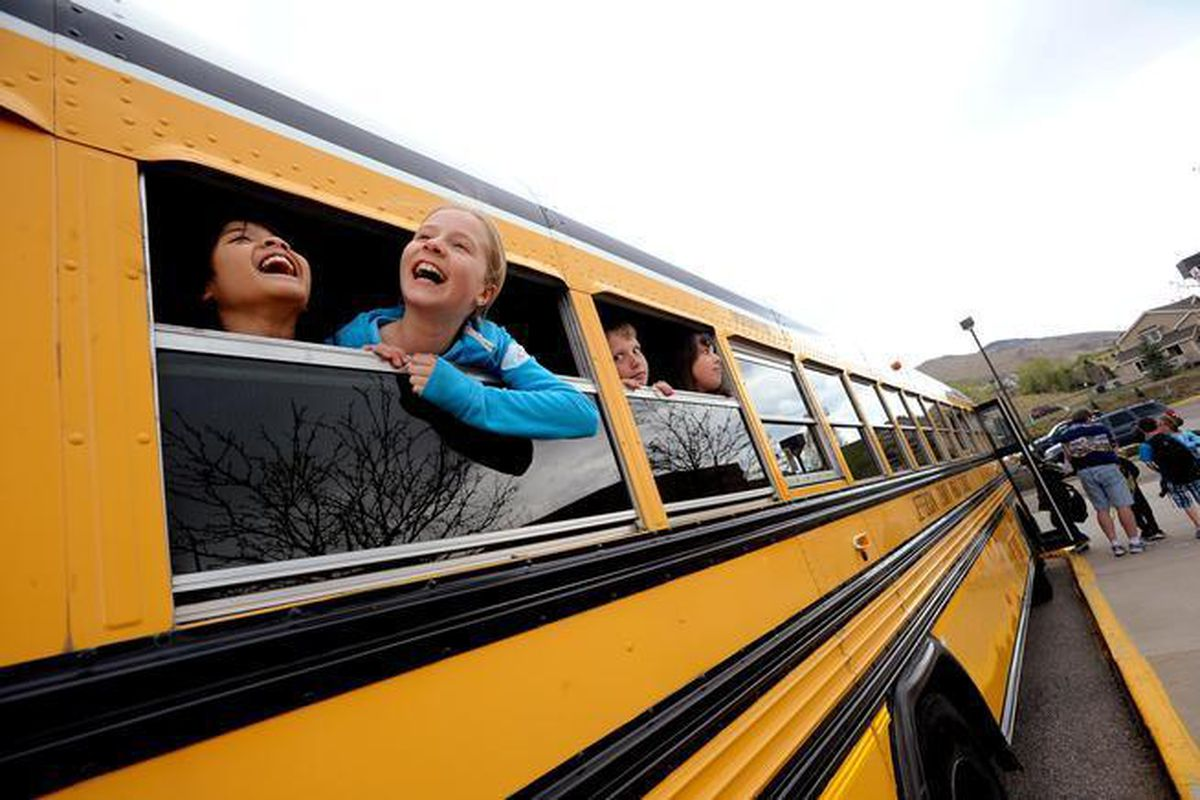 Fourth-graders Kintan Surghani, left, and Rachel Anderson laugh out the school bus window at Mitchell Elementary School in Golden.