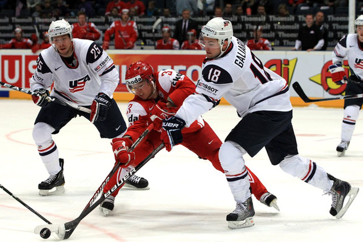 T J Galiardi #18 of USA and <strong>Philip Larsen</strong> #3 of Denmark battle for the puck during the IIHF World Championship.