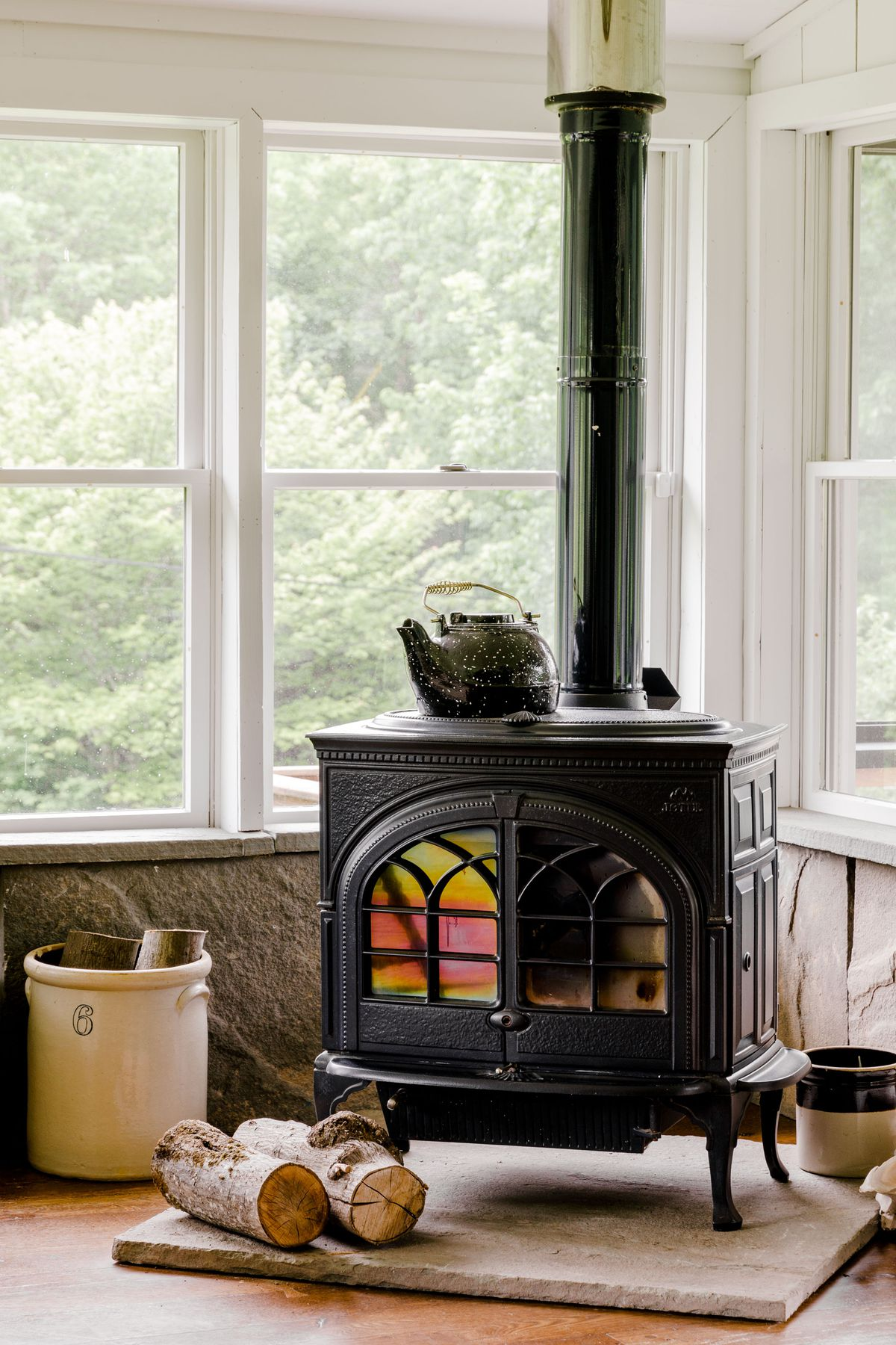 Windows overlooking trees surround a black woodstove with tree logs on the floor