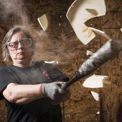 Shawn Baker, the owner of Tantrums, smashes a dinner plate in a destruction room at Tantrums in Houston on Saturday, July 15, 2017. Tantrums is a business where people can let off steam by using bats, poles, golf clubs and sledge hammers to destroy TVs, mirrors, cups, sheets of glass and more. Baker started Tantrums after she was laid off from her job in the oil industry, and she said her business acts as therapy to some and fun for others.