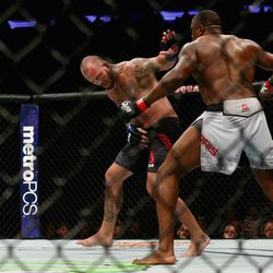 In an odd fight, Mark Godbeer reels from a knee to the groin while Walt Harris pursues.
